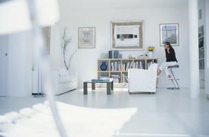 白いソファや本棚のあるリビングでイスに座る女性の写真素材 [FYI03230607]