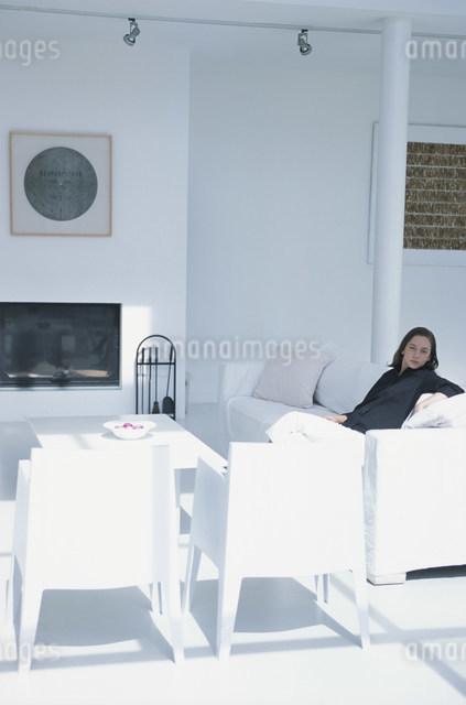 白いイスやソファセットのあるリビングで寛ぐ女性の写真素材 [FYI03230613]