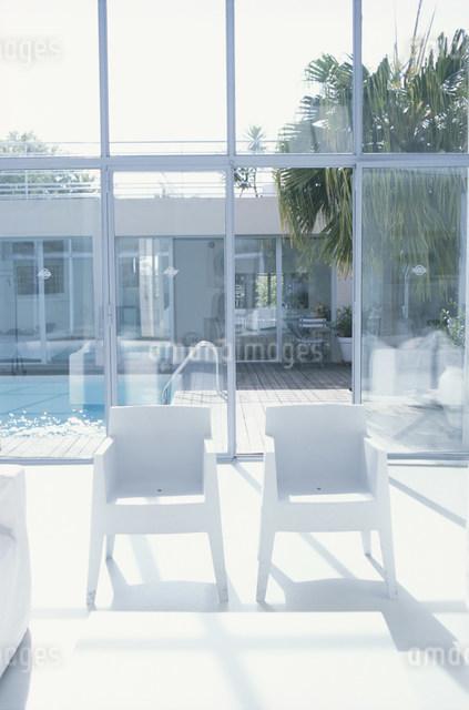 白いイス越しに見える屋外のプールサイドの写真素材 [FYI03230616]