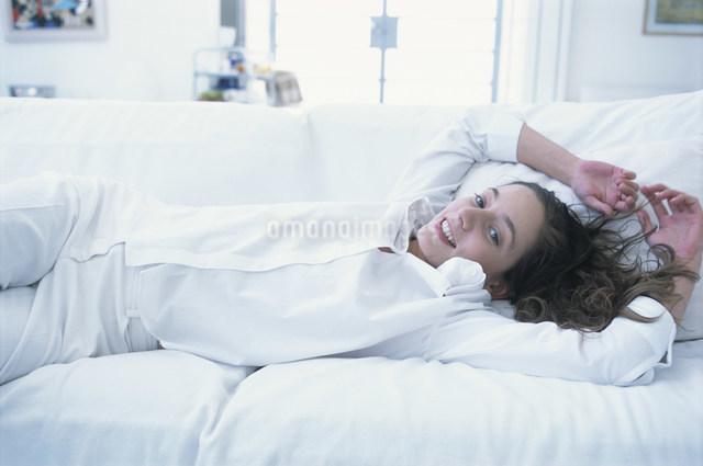 白いソファセットの上に横たわる女性の写真素材 [FYI03230619]