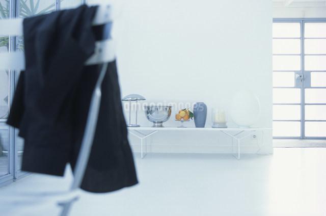 イスにかかったシャツと奥に置かれた花瓶やフルーツの写真素材 [FYI03230623]