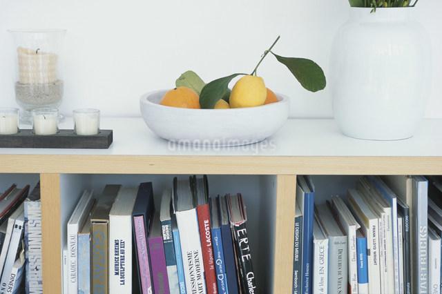 フルーツやロウソクを置いた本棚の写真素材 [FYI03230626]