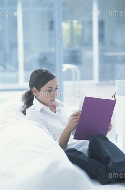 白いソファに座って本を読む女性の写真素材 [FYI03230635]