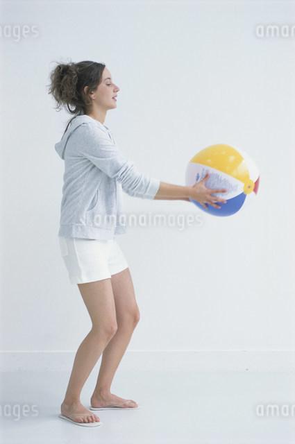 ビーチボールを持った女性の写真素材 [FYI03230638]