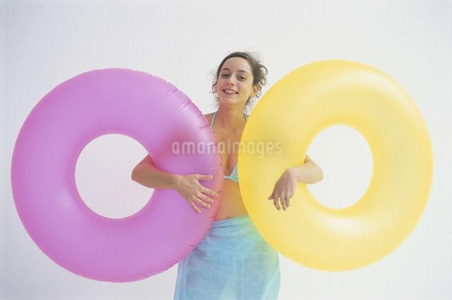 カラフルな浮き輪を持った水着の女性の写真素材 [FYI03230639]