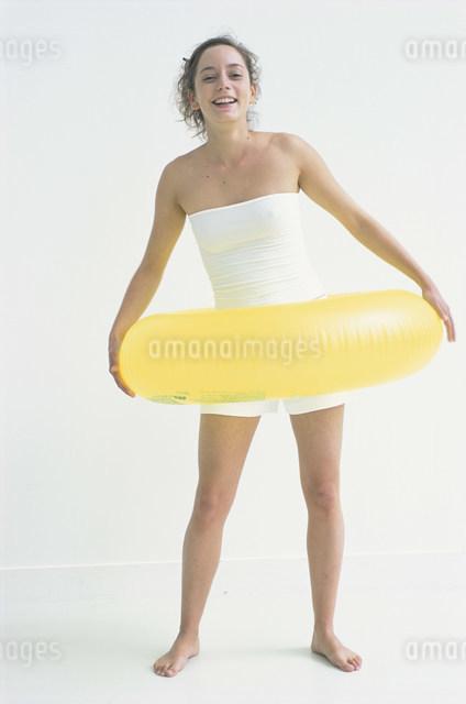 黄色の浮き輪を持った白いウェアの女性の写真素材 [FYI03230640]