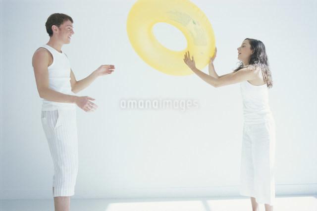 黄色の浮き輪で遊ぶ男女の写真素材 [FYI03230644]
