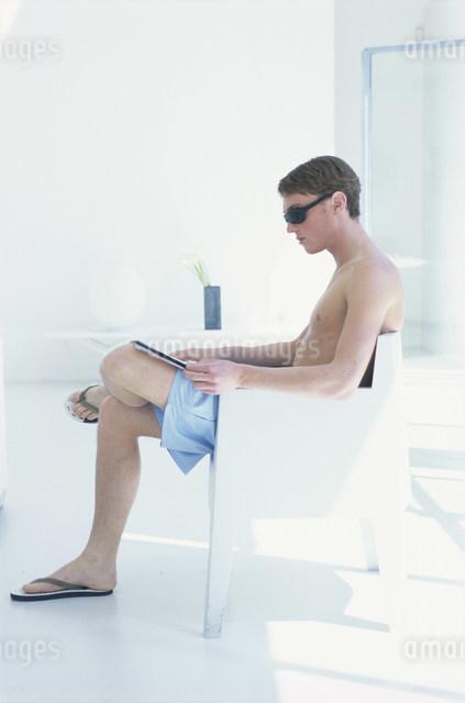 ソファで本を読むサングラスの男性の写真素材 [FYI03230650]