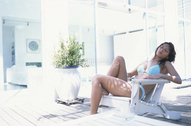 デッキチェアに座って眠る水着の女性の写真素材 [FYI03230652]
