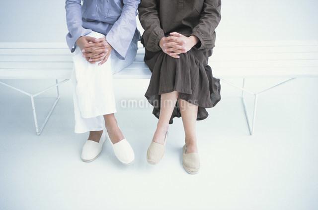 並んで座る女性2人の足元の写真素材 [FYI03230666]
