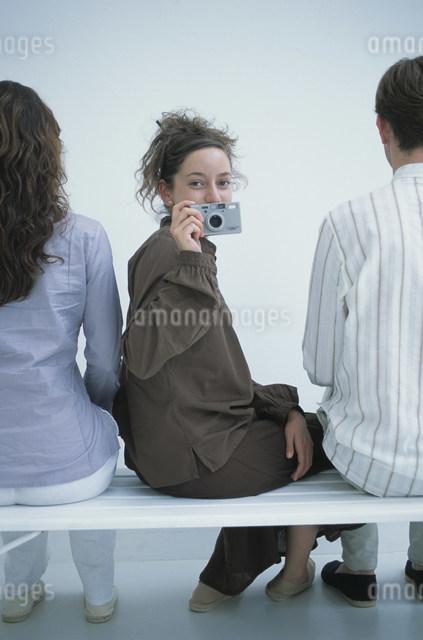 カメラを構えて振り返る女性と後姿の男女の写真素材 [FYI03230670]