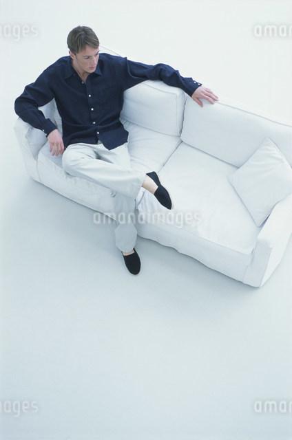 白いソファに座って寛ぐ男性の写真素材 [FYI03230671]