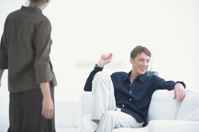 白いソファに座って笑う男性と前に立つ女性の写真素材 [FYI03230672]