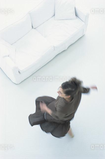 白いソファのある部屋で動く女性の写真素材 [FYI03230673]