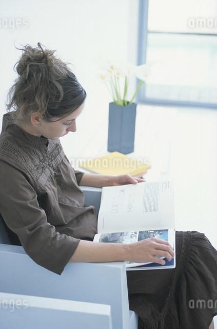 白いイスに座って本を読む女性の写真素材 [FYI03230681]