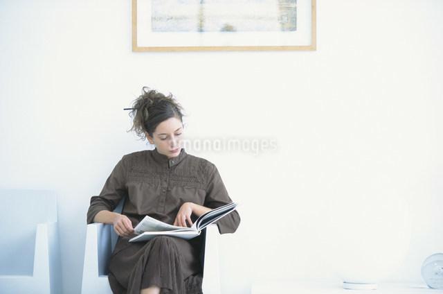 白いイスに座って本を読む女性の写真素材 [FYI03230682]