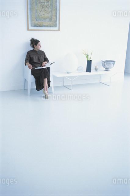 壁際に置いた白いイスに座って本を開く女性の写真素材 [FYI03230686]