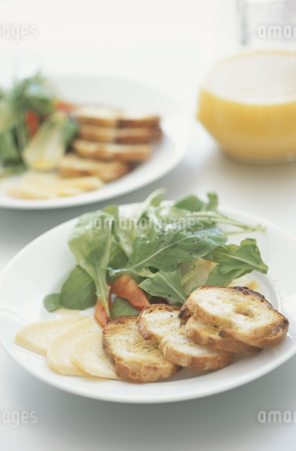皿に盛ったリーフサラダとパンとチーズの写真素材 [FYI03230714]
