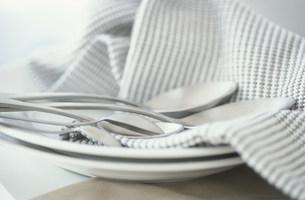 白い皿にのせたナフキンとスプーンの写真素材 [FYI03230717]