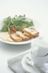 皿に盛ったリーフサラダとパンとチーズと白いカップの写真素材 [FYI03230722]