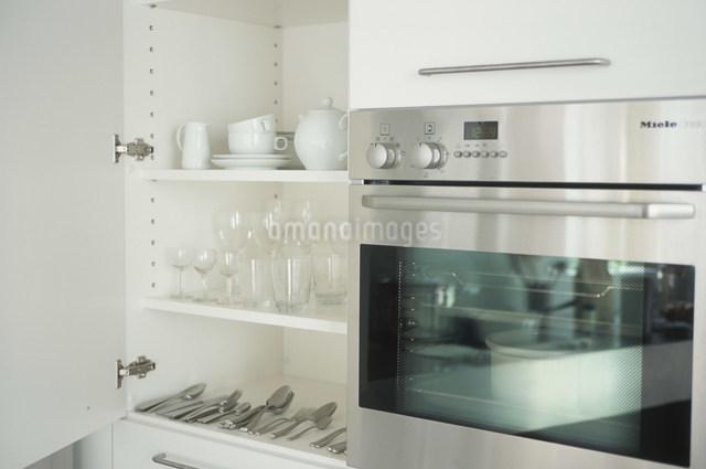 食器棚に整頓された食器類とオーブンの写真素材 [FYI03230723]