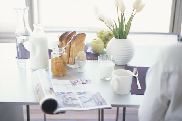 朝食と雑誌を置いたテーブルの写真素材 [FYI03230735]