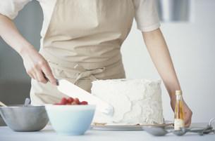 シフォンケーキにクリームを塗る女性の写真素材 [FYI03230756]