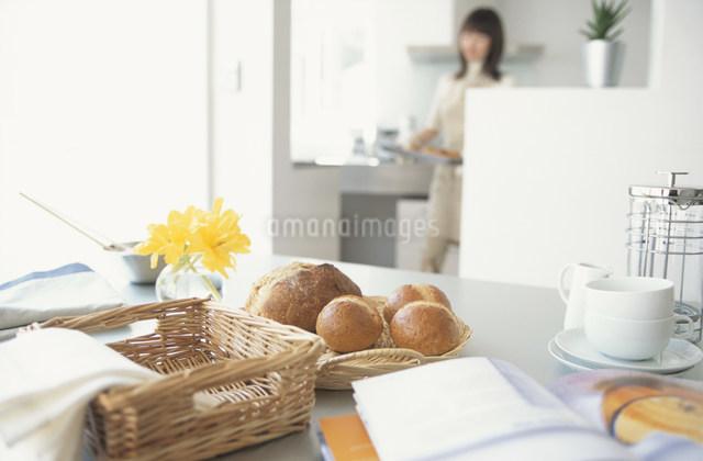 焼き上がりのパンを運ぶ女性と焼き立てパンの写真素材 [FYI03230757]