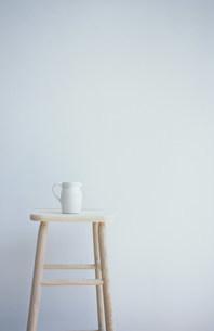 白木のスツールにのせた白い水差しの写真素材 [FYI03230784]