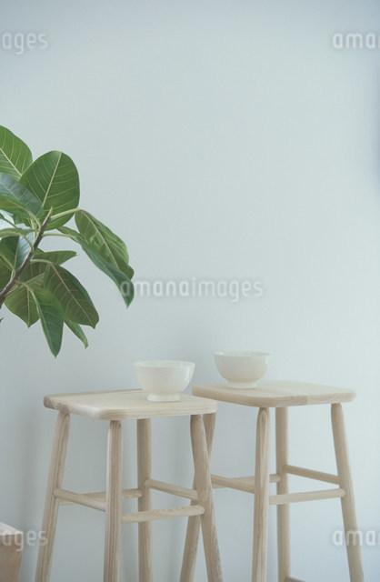 白木のスツールにのせた白い陶器のボールの写真素材 [FYI03230788]