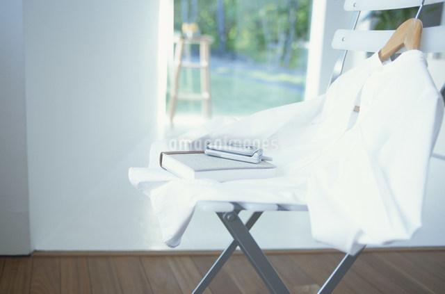 イスに置いた白いシャツと本と携帯の写真素材 [FYI03230791]