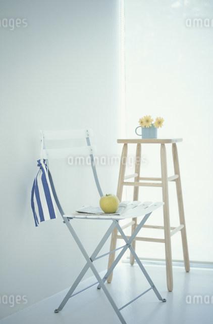 青リンゴをのせたスチールイスと花をのせたスツールの写真素材 [FYI03230827]