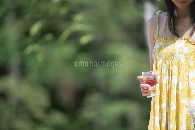 カシスジュースの入ったグラスを持つ女性の写真素材 [FYI03230835]