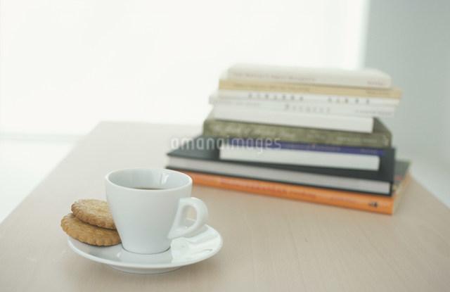 クッキーを添えた白いコーヒーカップと本の写真素材 [FYI03230841]
