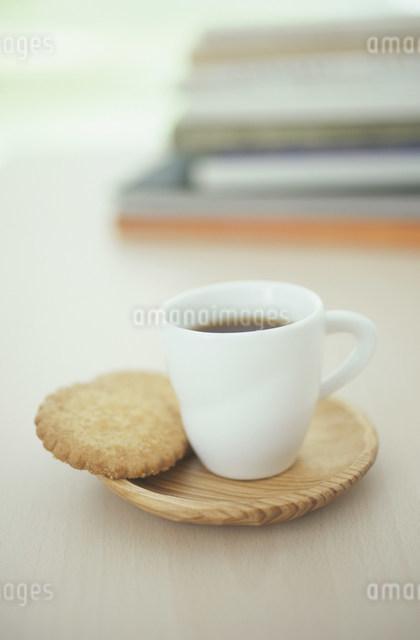 クッキーを添えた木のソーサーと白いコーヒーカップの写真素材 [FYI03230842]