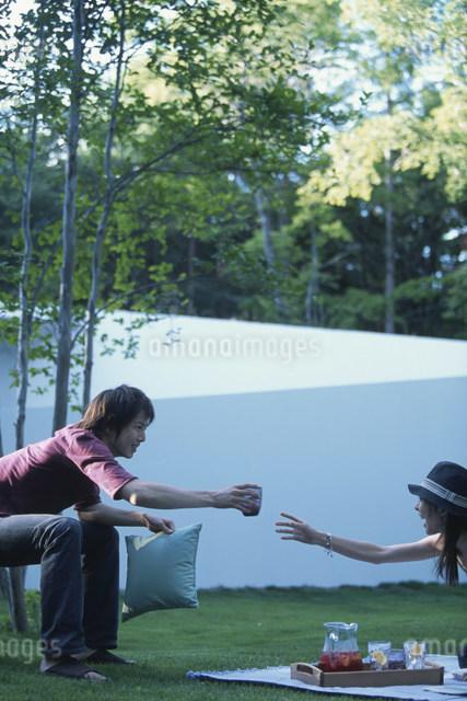 庭でジュースを渡す日本人カップルの写真素材 [FYI03230846]