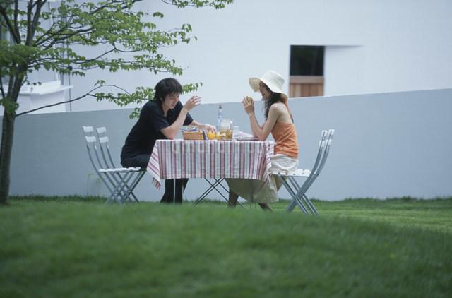 ガーデンテーブルで談笑する日本人カップルの写真素材 [FYI03230853]