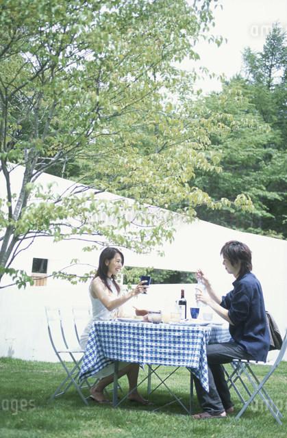 ガーデンテーブルで食事を楽しむ日本人カップルの写真素材 [FYI03230864]