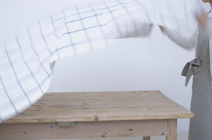 テーブルクロスを敷く女性の写真素材 [FYI03230909]