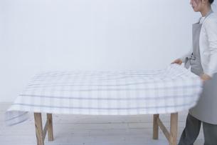 テーブルクロスを敷く女性の写真素材 [FYI03230914]