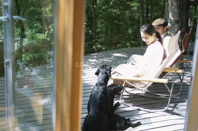 テラスでくつろぐ2人と犬の写真素材 [FYI03231038]
