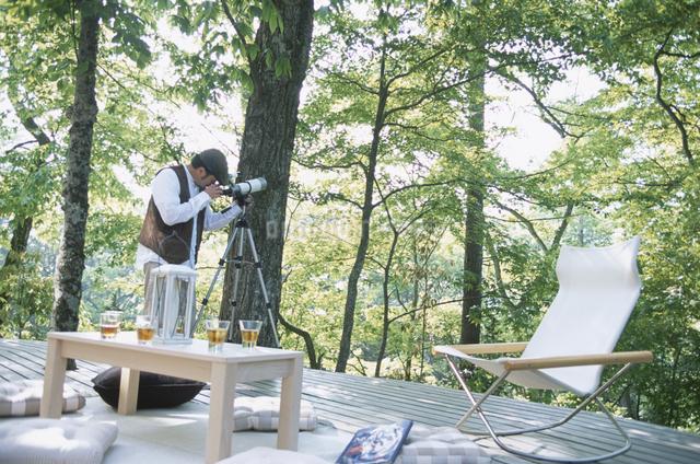 望遠鏡を覗く男性の写真素材 [FYI03231052]