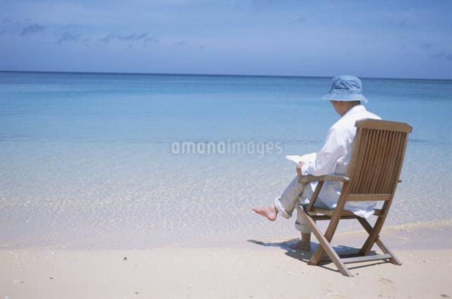 砂浜で本を読む男性の写真素材 [FYI03231149]