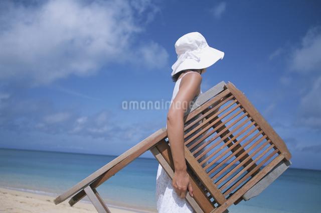 椅子を抱えて砂浜を歩く女性の写真素材 [FYI03231153]
