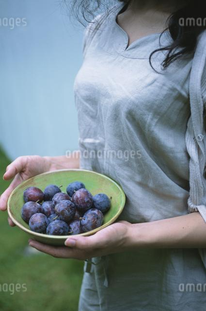 プルーンを持つ女性の写真素材 [FYI03231303]