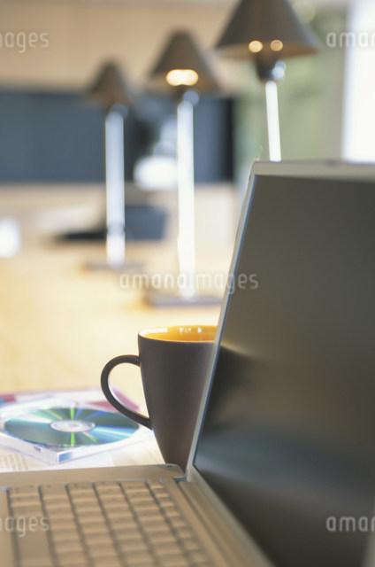 コンピュータの近くに置かれたマグカップやCDなどの写真素材 [FYI03231380]