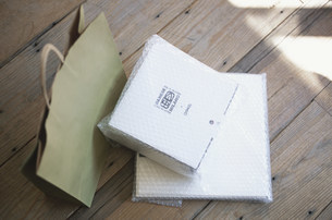 床に置いた緑の紙袋とエアパッキンされた箱の写真素材 [FYI03231418]
