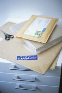 引出しの上に置いた郵便物と鋏の写真素材 [FYI03231442]