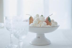 器に盛ったメレンゲ菓子と果実の形のキャンドルの写真素材 [FYI03231455]