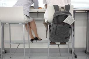 窓辺のデスクに座る女性と男性の後姿の写真素材 [FYI03231521]